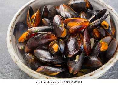 Mussels cooked in wine sauce with herbs in bowl on concrete background.