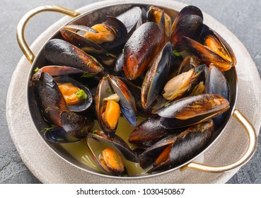 Mussels cooked in wine sauce with herbs in a frying pan on concrete background.