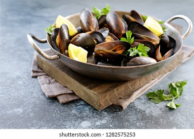 Mussels in cooking dish with parsley and lemon. Close up view