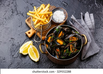 Mussels in copper cooking dish and french fries on black stone background
