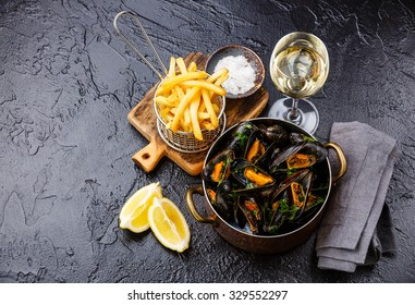 Mussels in copper cooking dish with wine and french fries on black stone background