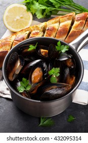 Mussels in copper pot and homemade bread on stone table