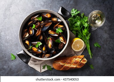 Mussels in copper pot and white wine on stone table. Top view