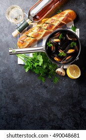Mussels in copper pot and white wine on stone table. Top view with copy space