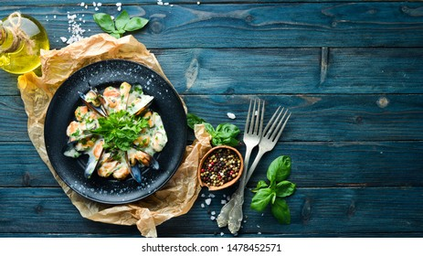 Mussels in cream sauce with basil. In the old background. Top view. Free copy space.
