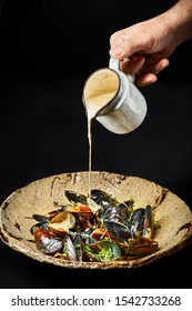 Mussels in creamy white sauce at black background. Chefs hand pours mussels from a jug. Seafood dish