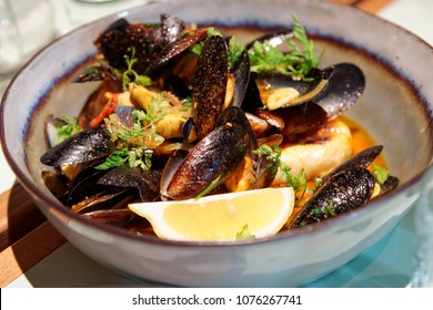 Mussels in a deep clay bowl with turmeric sauce and lemon
