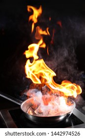 Mussels flamb in the pan. Cooking in front of visitors, shows. Flame over the pan.