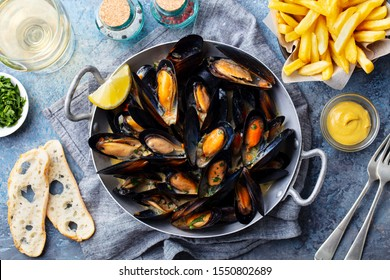 Mussels with french fries and white wine in cooking pan. Grey background. Top view.