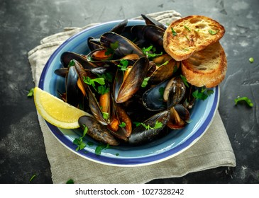Mussels in garlic butter sauce served with parsley, toast and lemon