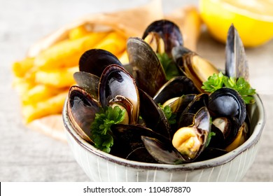 Mussels with herbs in a bowl with lemon and French fries on a white wooden board. Seafood. Food at the shore of the French Sea. Dark background