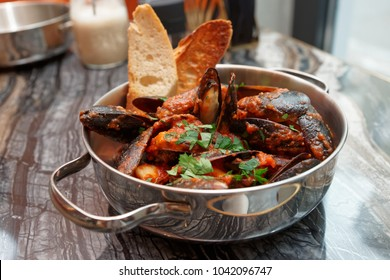 Mussels with hot Italian arrabiata sauce and served in metal pot