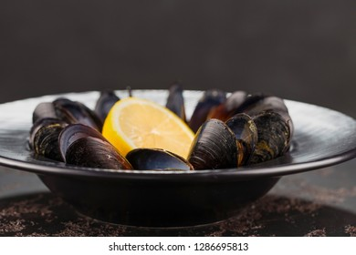 Mussels on a black plate in wine with half a lemon. Seafood. Clams in the shells. Delicious snack for gourmands. Selective focus