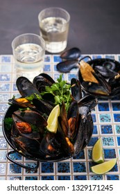 Mussels in a pan with parsley and lemon on a dark background. Top view.Seafood, mediterranean food.