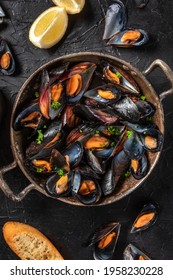 Mussels in a pan, shot from the top with lemon and toasted bread