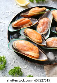 Mussels in a round plate on a light gray background