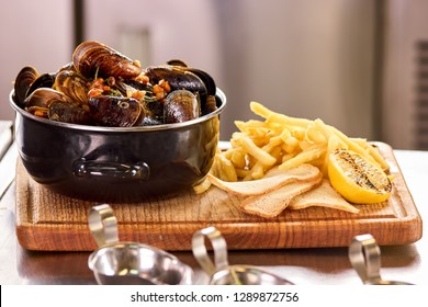 Mussels in saucepan and fries. Belgian mussels in white wine with tomatoes, croutons and french fries.