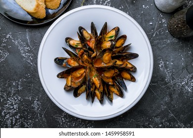 Mussels in tomato sauce on white plate