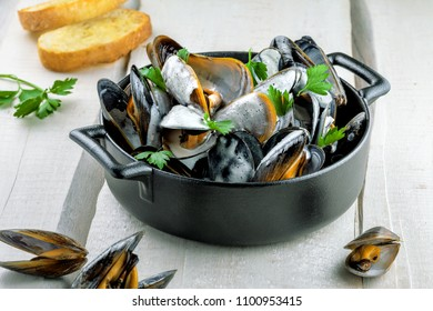 Mussels in a white wine and cream sauce on a table. Classic French meal Moules marinière.