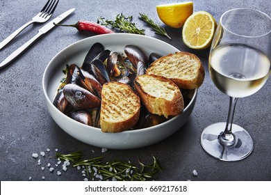 mussels in white wine sauce with glass of white wine  white bread toasts, decorated with hilly pepper, lemon and sea salt