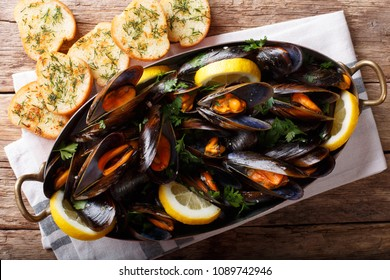Mussels in wine with parsley and lemon. Seafood. Clams in the shells. Delicious snack for gourmands. horizontal top view from above, rustic style