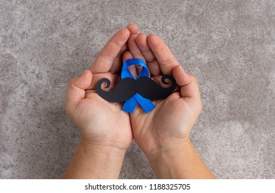 Mustache pattern with blue ribbon symbol in child's hands on the gray slate background. November concept. Prostate Cancer and men's health awareness.