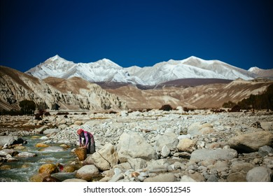 MUSTANG, NEPAL-OCTOBER 22, 2019 : Woman washing in the river , 22 October 2019