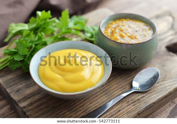 La moutarde dans l'assortiment : Moutarde de Dijon et moutarde russe en feu dans des bols sur fond bois