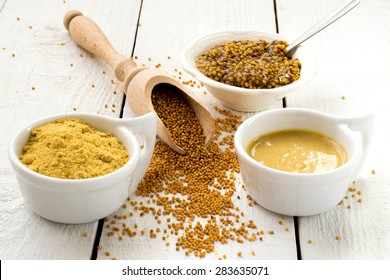 Mustard in the assortment: powder, grain in the wooden spoon, Dijon mustard, burning Russian mustard on a white wooden table. Selective focus