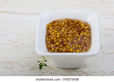 Mustard dijon in the bowl on wood bacground