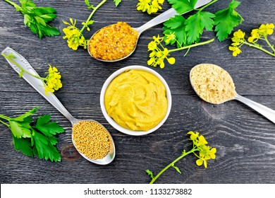Mustard granular, powder, seeds in spoons and mustard sauce in a bowl, yellow flowers and parsley on the background of a wooden board from above