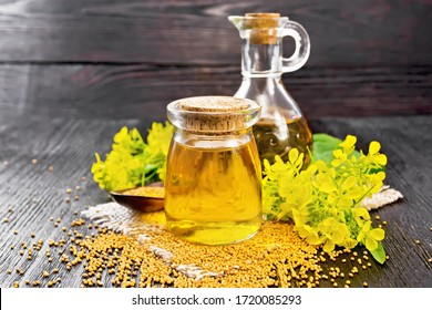Mustard oil in a glass jar and decanter, mustard grains on a burlap napkin, flowers and leaves on wooden board background