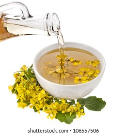 Mustard  oil  pour in a bowl with mustard flower bloom isolated on white