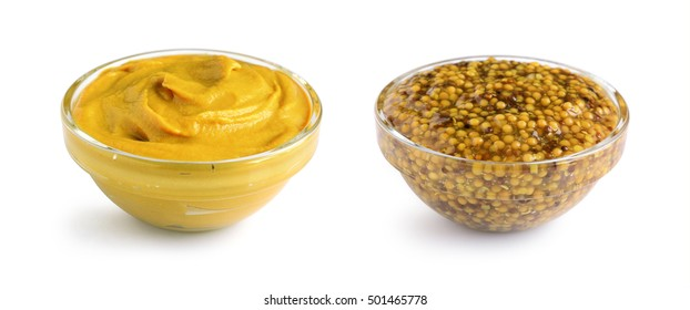 Mustard sauce and wholegrain mustard in two glass bowls isolated on white