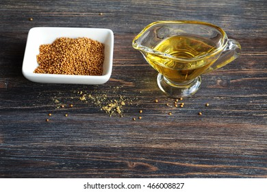 Mustard seeds and mustard oil on a wooden table. Special light.