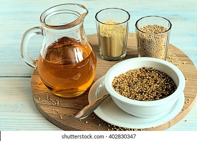 Mustard seeds, mustard powder, mustard oil in glassware and mustard in a white  cup on a wooden board