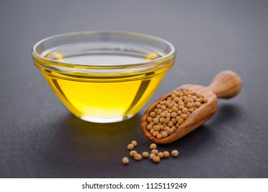 mustard seeds in a wooden scoop and glass bowl with oil on dark background