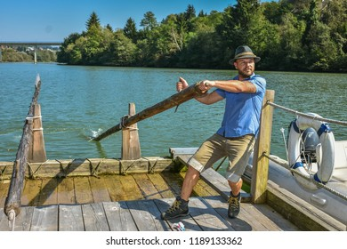 MUTA, SLOVENIA - SEPTEMBER 21th 2018: The man (flosar) guiding the wooden raft (flos) for transporting the wood on the Drava river as in old times