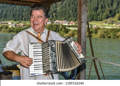 MUTA, SLOVENIA - SEPTEMBER 21th 2018: The musician playing on the raft floating on Drava river entertaining tourists
