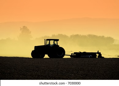 Muted Backlit Silhouette of Tractor Raking Soil