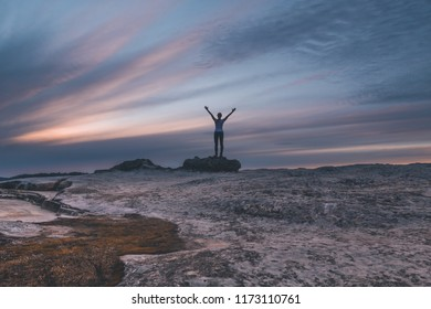 Muted tones of the sunset skies from Lincolns Rock Kings Tablleland. A woman stands with windblown hair and arms outstretched to the sky in awe or praise