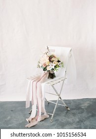 Muted Wedding Bouquet with Pink and Purple Flowers Sits on a White Bistro Chair