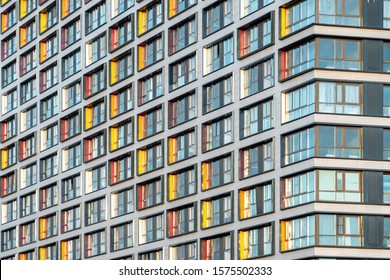 Muticolor facade of a residential multi-storey building with large windows. Modern architecture. Real estate in a big city. Background from the wall of the house.