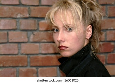 the mutinous blonde against the background of the wall from the brick
