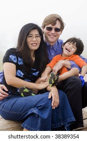 Mutiracial family sitting on beach on misty, foggy day.