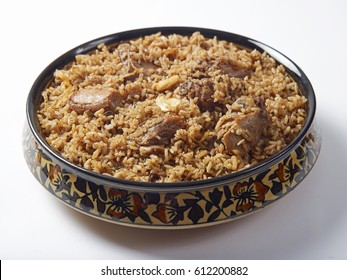 mutton biriyani served in a serving bowl on white background