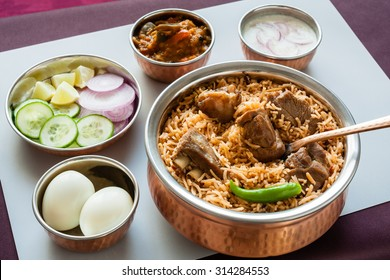 Mutton biryani with traditional sides - Closeup view from the top of delicious mutton (lamb) biryani served in authentic copper utensils with salad (raita), gravy and egg. Natural light used.