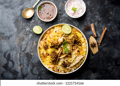 mutton or lamb biriyani with basmati rice, served in a bowl over moody background.