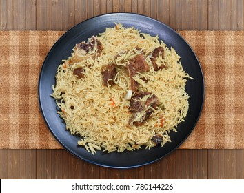 Mutton Pulao on wooden table in black plate