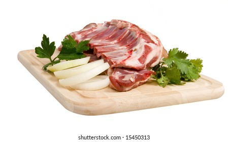 Mutton-chop with herbs and onion on board on white ground